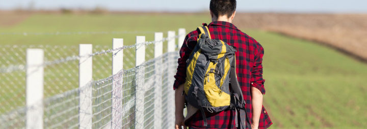 understanding type of temporary residencies - boy with backpack walking along fence line